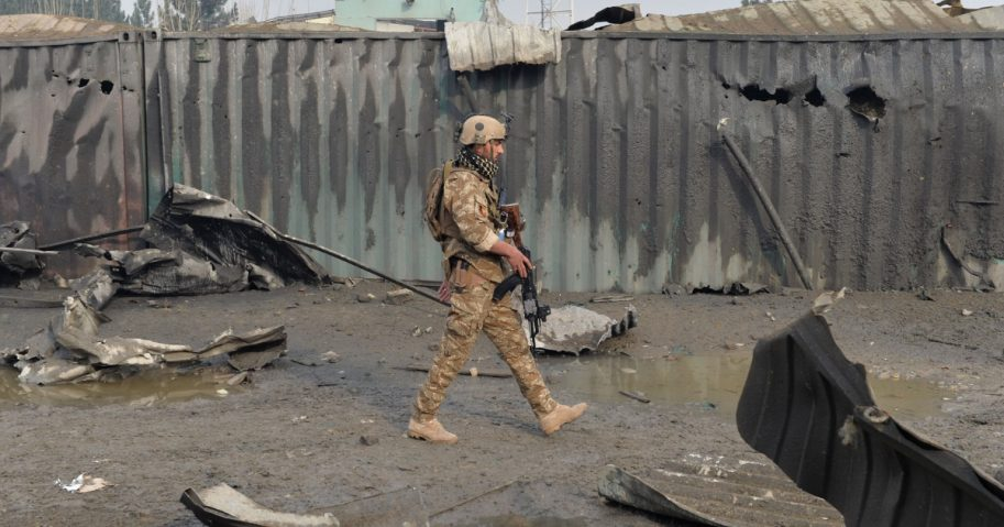 A member of the Afghan security forces walks at the site of a suicide bomb attack outside a British security firm's compound in Kabul.