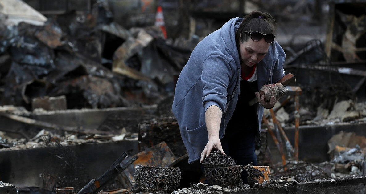 Woman looks through the remains of her home that was destroyed by the Camp Fire on November 22, 2018 in Paradise, California.