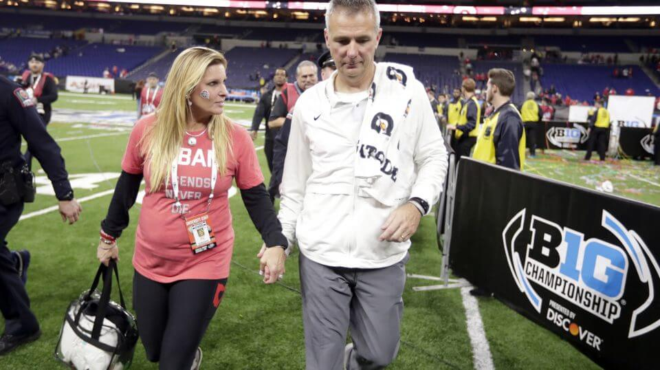 Ohio State head coach Urban Meyer walks off the field with his wife, Shelley Meyer, early Sunday after the Buckeyes defeated Northwestern in the Big Ten championship game in Indianapolis.