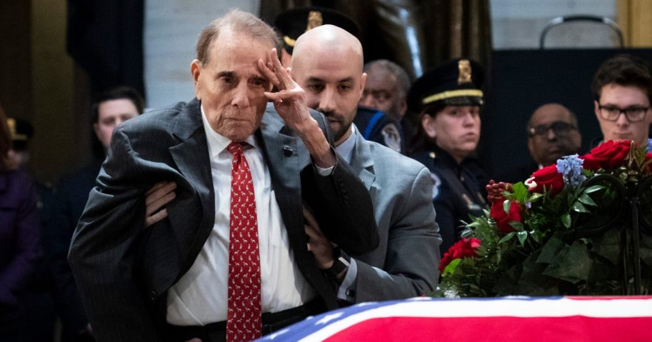 Former Senator Bob Dole stands up and salutes the casket of the late former President George H.W. Bush as he lies in state at the U.S. Capitol.