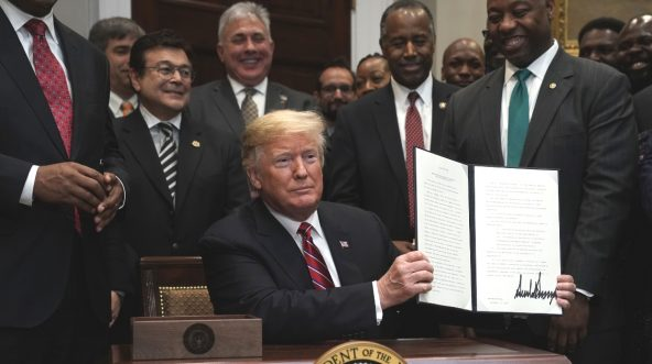 President Donald Trump participates in signing an executive order to establish the White House Opportunity and Revitalization Council as Secretary of Housing and Urban Development Secretary Ben Carson and Sen. Tim Scott look on.
