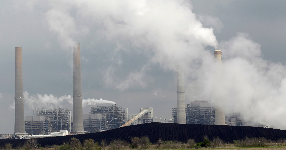 In this March 16, 2011, photo, exhaust rises from smokestacks in front of piles of coal at NRG Energy's W.A. Parish Electric Generating Station in Thompsons, Texas.