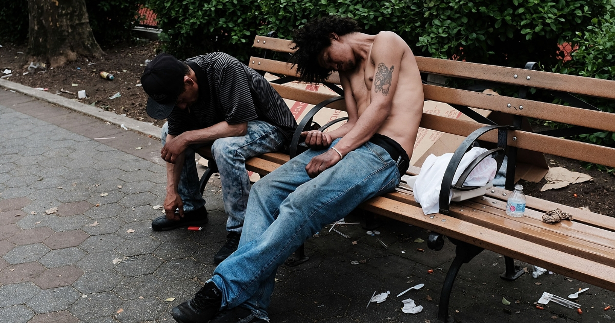 Men sit passed out in a park where heroin users gather to shoot up in the Bronx.