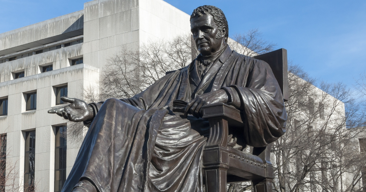 Bronze statue of John Marshall, fourth chief justice of the Supreme Court, located in John Marshall Place Park with U.S. Supreme Court building in background in Washington D.C.