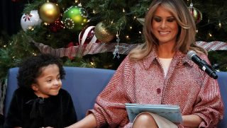 U.S. first lady Melania Trump shares a moment with patient escort Tearrianna Cooke-Starkey while reading the story 'Oliver the Ornament' during a visit to the Children's National Hospital.