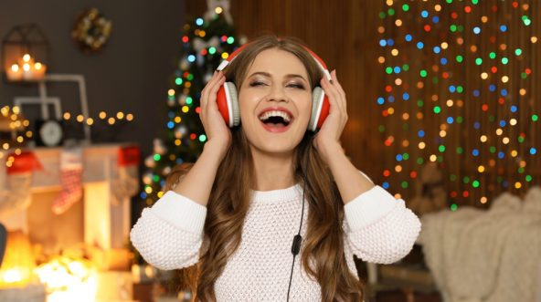 Happy young woman listening to Christmas music at home