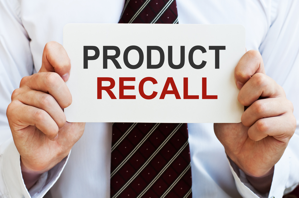 Product Recall. Man holding a card with a message text written on it - Image