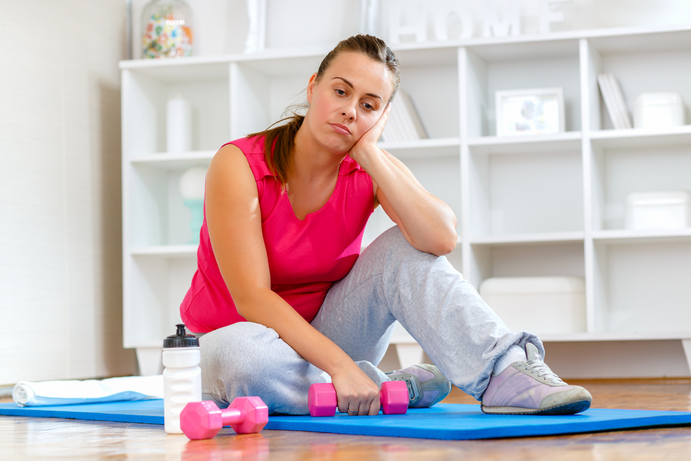 Tired young woman struggling to get back into shape.