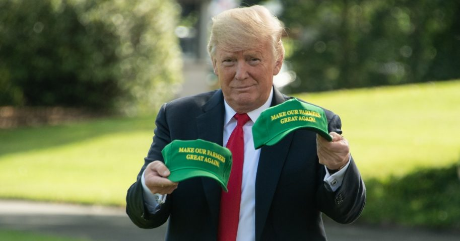 US President Donald Trump displays caps reading 'Make our Farmers Great Again'