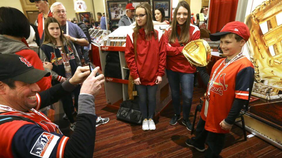Maryland, snaps a photo of his son Caleb, 9, wearing St. Louis Cardinal catcher Yadier Molina's 2018 Golden Glove that was on display at the Cardinals Care Winter Warm-Up on Jan. 19, 2019, in St. Louis, Missouri.