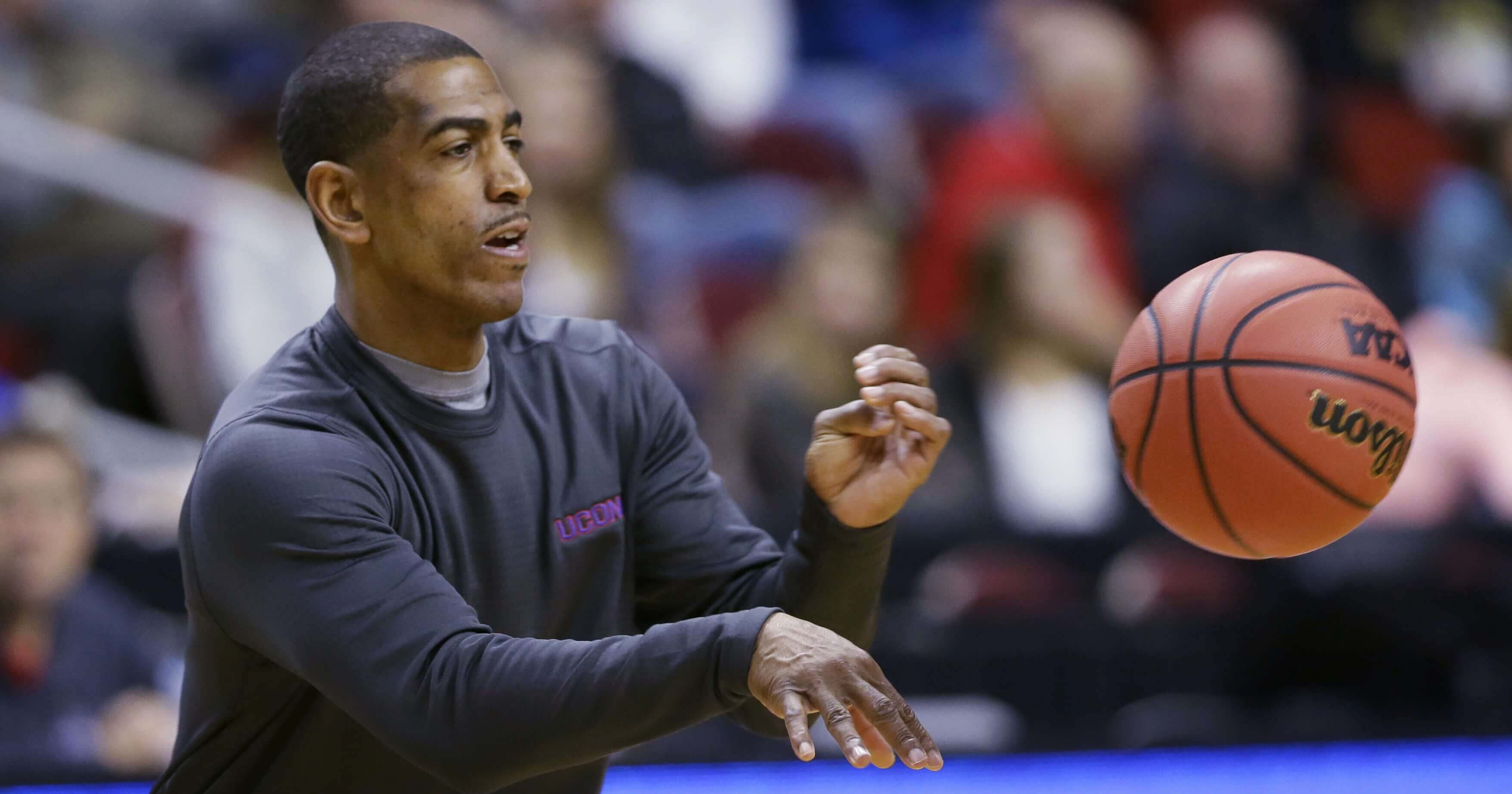 Coach Kevin Ollie passes the ball during UConn basketball practice March 16, 2016.