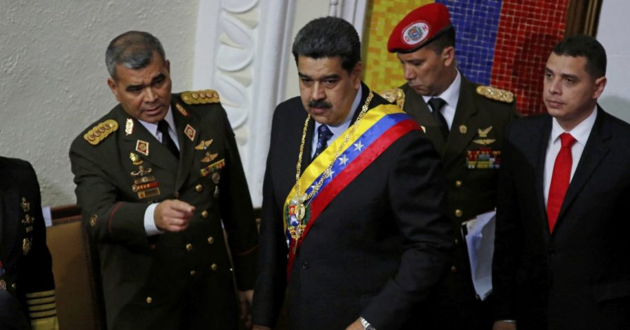 Venezuela's President Nicolas Maduro, center, stands with his Defense Minister Vladimir Padrino Lopez before giving his annual address to the nation to members of the Constitutional Assembly inside the National Assembly in Caracas, Venezuela, Jan. 14, 2019.
