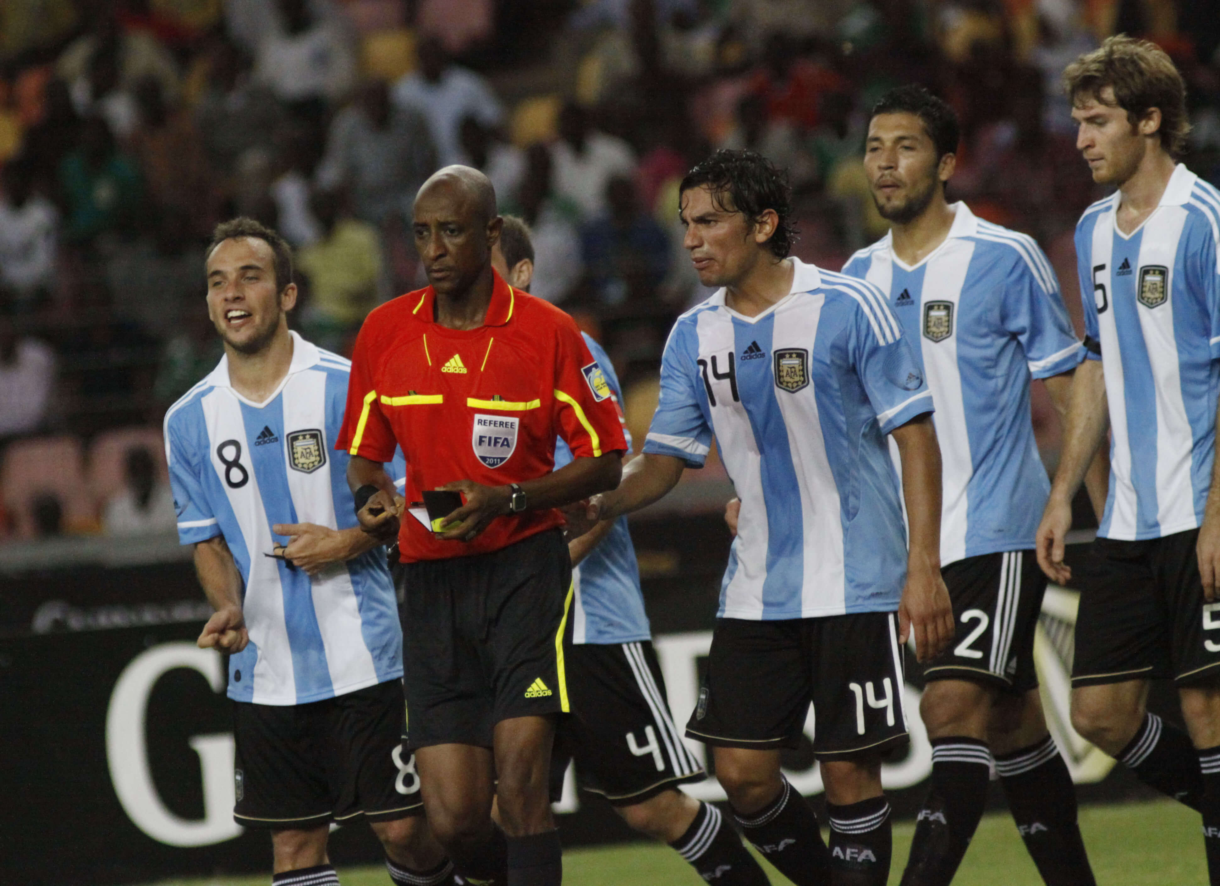 Referee Ibrahim Chaibou, second from left, is surrounded by Argentine soccer players after he awarded a penalty against them during an international friendly soccer match with Nigeria on June 1, 2011.