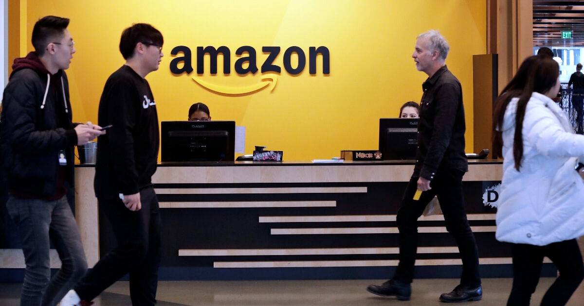 Employees walk through the lobby at Amazon's headquarters in Seattle.