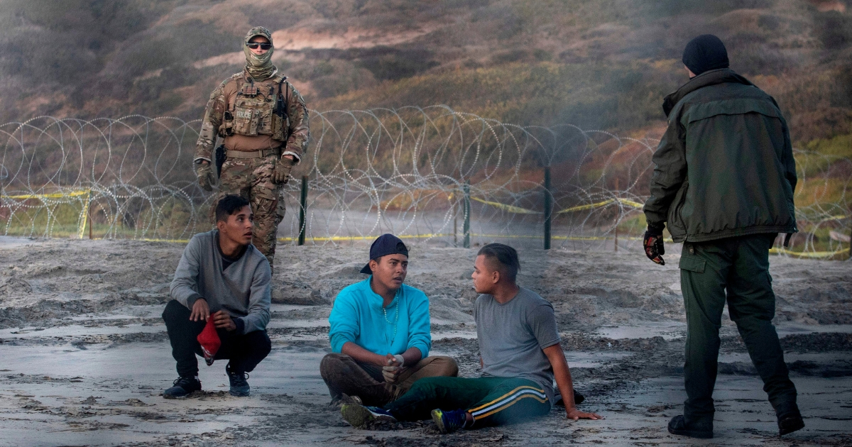 Central American migrants are taken into custody by U.S. Border Patrol agents after crossing illegally near San Diego on Dec. 13.