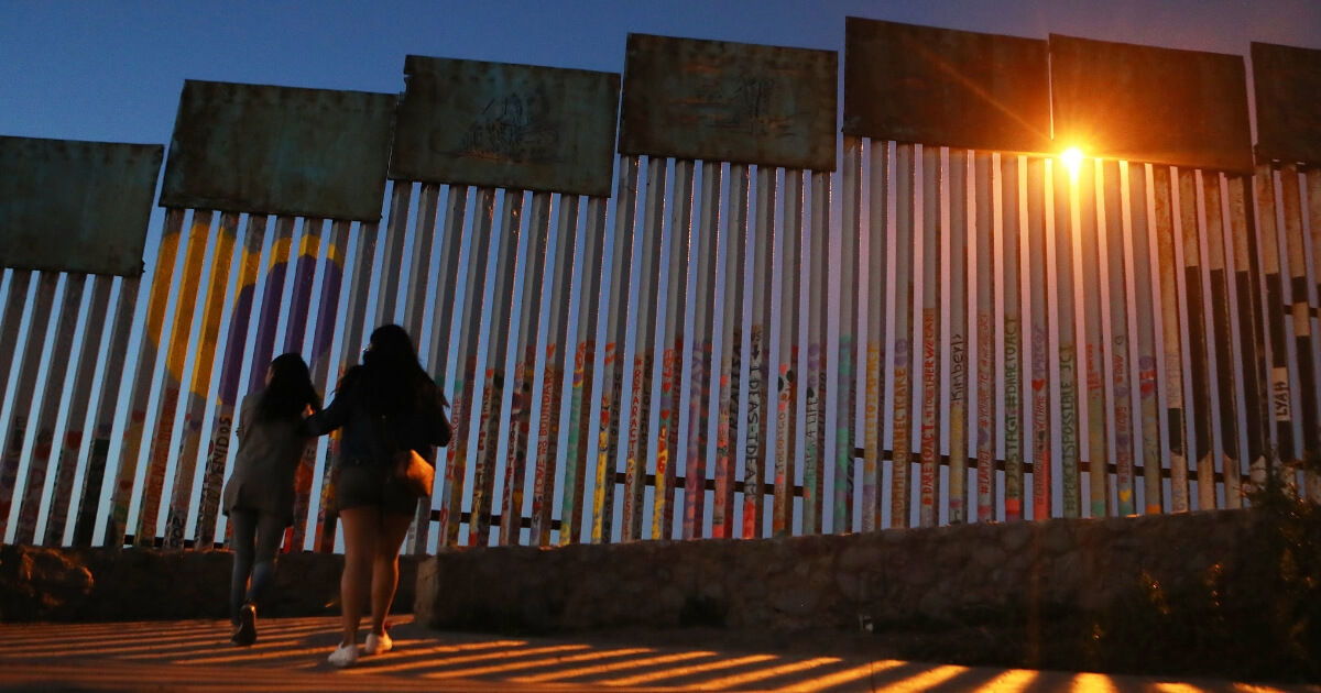 People walk on the Mexican side of the U.S.-Mexico border barrier