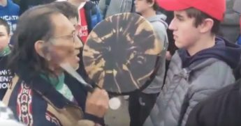 Native American man drums in front of student in MAGA hat.