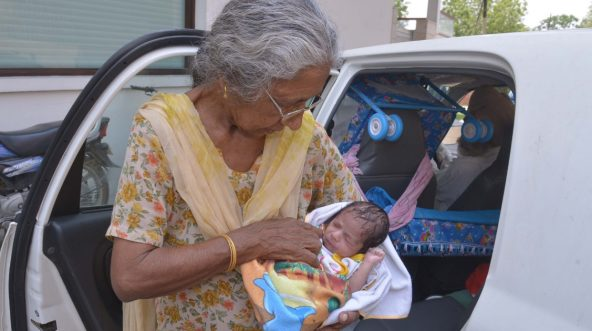 Indian mother Daljinder Kaur poses for a photograph as she holds her newborn baby boy Arman as she arrives home in Amritsar on May 11, 2016.