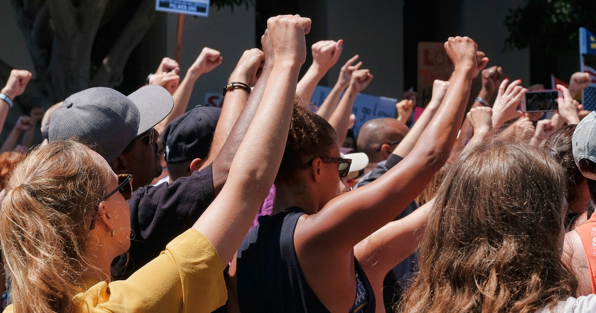 Demonstrators raise clenched fists in defiance to racism during a protest in the Venice beach area of Los Angeles on Aug. 19, 2017.