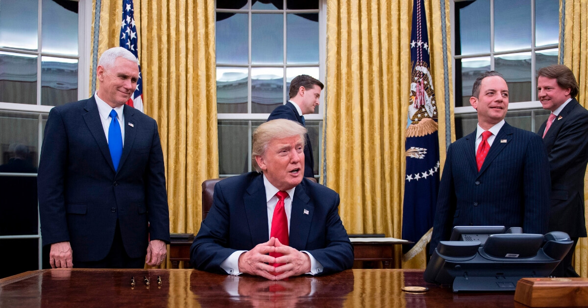 President Donald Trump (Center) speaks to the press as he waits at his desk before signing conformations on Jan. 20, 2017.