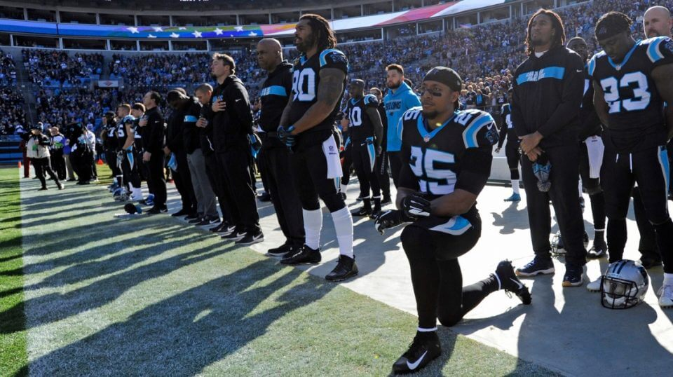 The Carolina Panthers' Eric Reid (No. 25) kneels during the national anthem before a Dec. 23 game against the Atlanta Falcons in Charlotte, North Carolina.