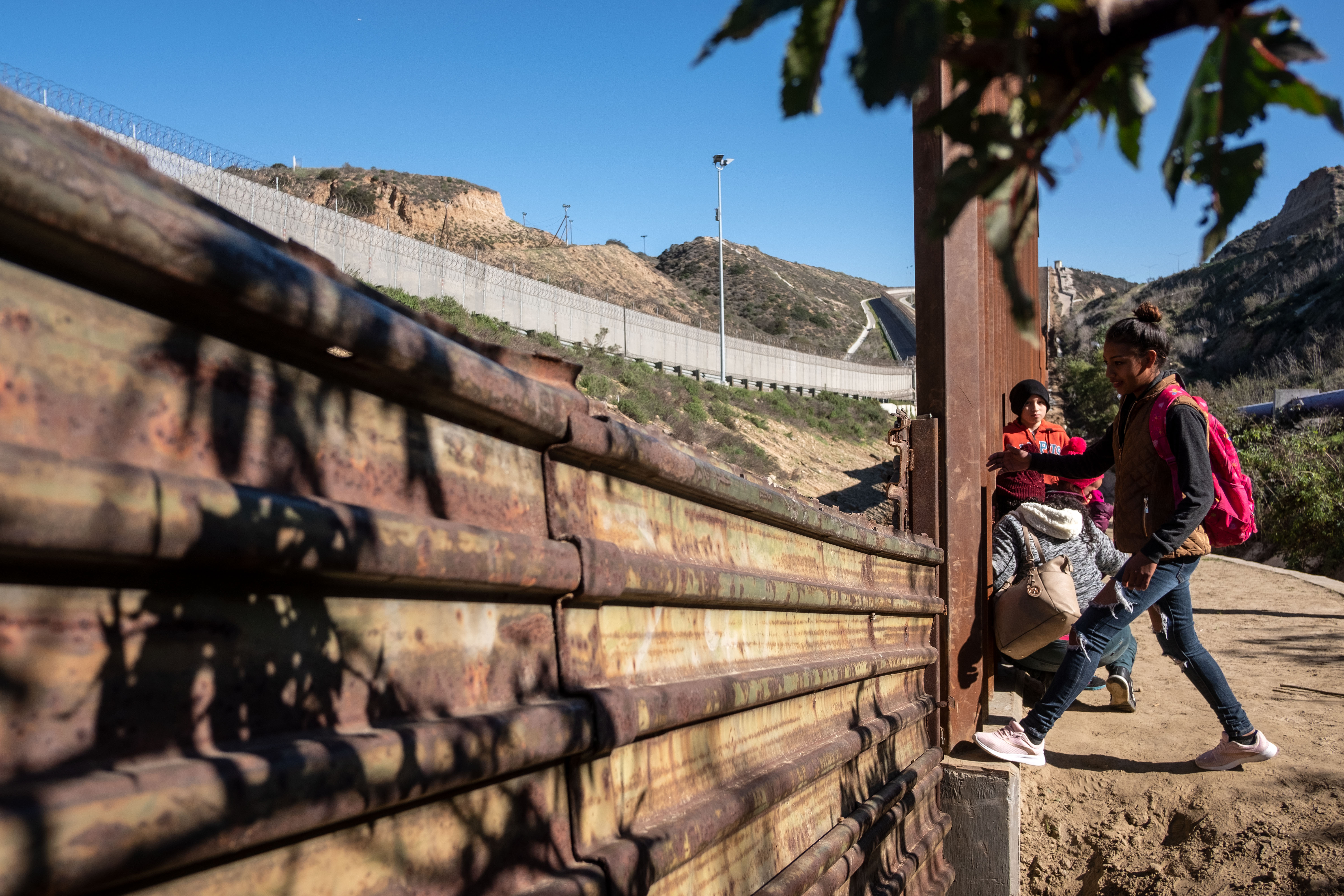 A 17-year-old Honduran migrant starts climbing the US-Mexico border fence