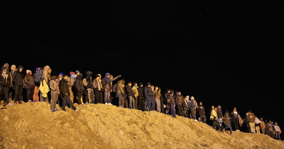 A group of Central American migrants wait to jump over the wall