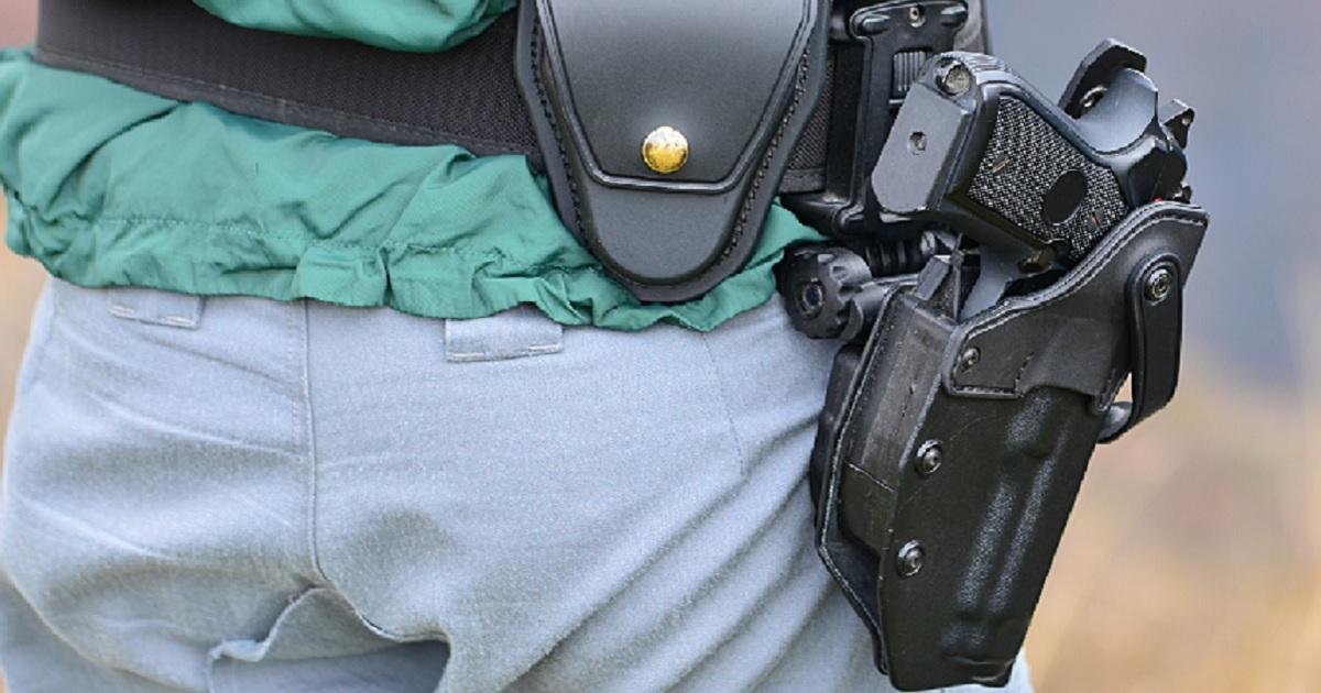 Gun in holster on man's hip.