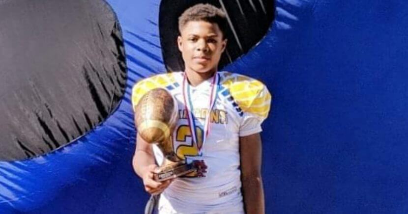 Southfield, Michigan, seventh-grade quarterback Isaiah Marshall holds a trophy.