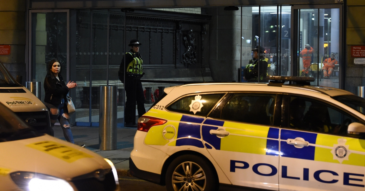 Police officers stand near a cordon at Manchester Victoria Station in the British city of Manchester on Tuesday following a New Year's Eve stabbing.