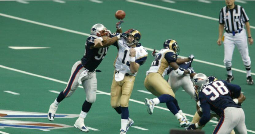 Roman Phifer #95 of the New England Patriots breaks a pass by quarterback Kurt Warner #13 of the St.Louis Rams during Superbowl XXXVI at the Superdome in New Orleans, Louisiana. The Patriots defeated the Rams 20-17.