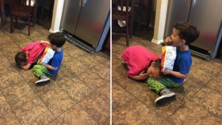 A brother and sister sitting on the kitchen floor.