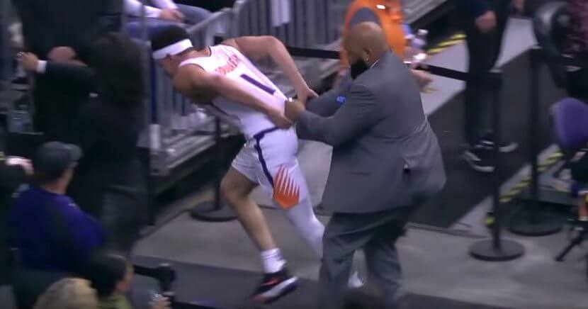 A security guard at Talking Stick Resort Arena tries to restrain the Phoenix Suns' Devin Booker.