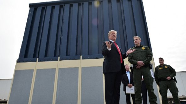 President Donald Trump with Border Patrol agents at a wall prototype.