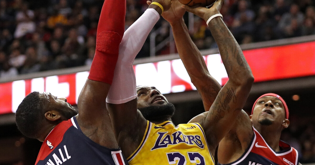 LeBron James of the Los Angeles Lakers is defended by John Wall and Bradley Beal of the Washington Wizards during a Dec. 16 game at Capital One Arena.