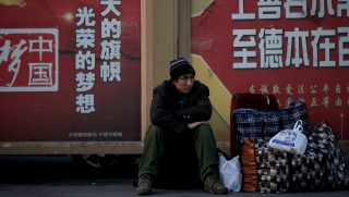 A migrant worker sits next to his belonging against a wall displaying a Chinese government propaganda message at the Beijing railway station in Beijing, Jan. 21, 2019.