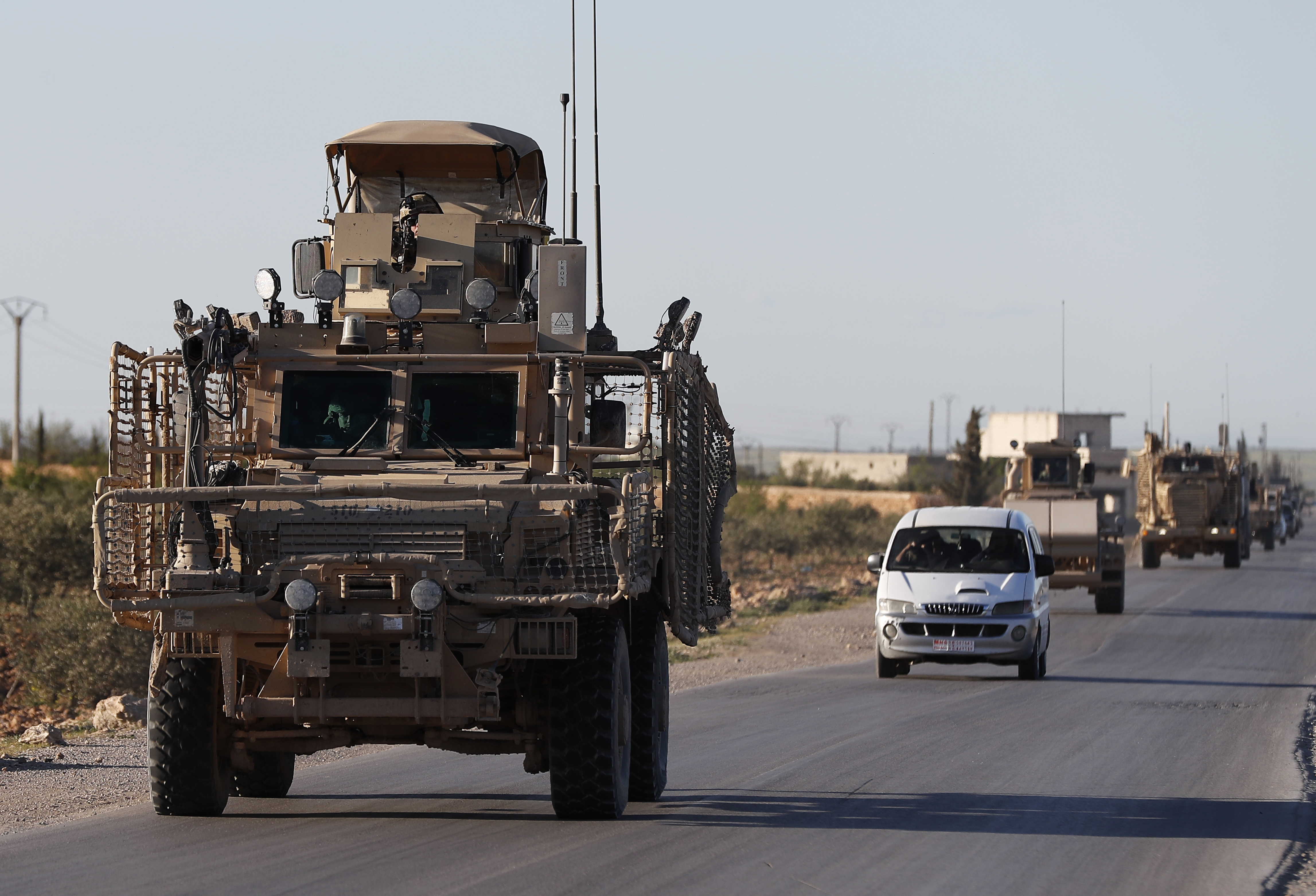 In this Saturday, March 31, 2018, file photo, a convoy of U.S. troops drive along a road leading to the front line with Turkish-backed fighters, in Manbij, north Syria.