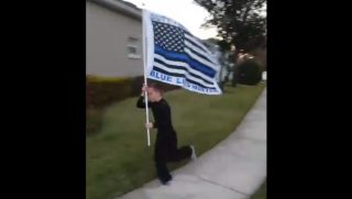Little boy running with police flag.