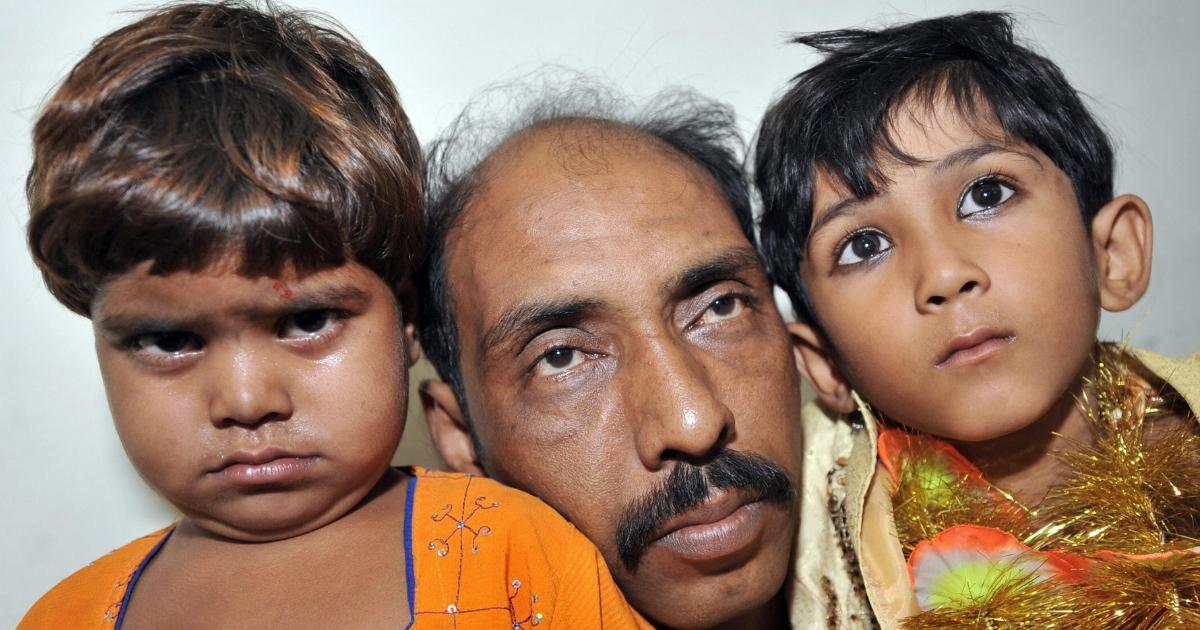 Muhmad Islamil, father of underage groom hold his ten year old son Muhmad Wasim and his three year old bride Nisha Nasir.