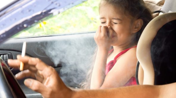 Child in car with parent smoking