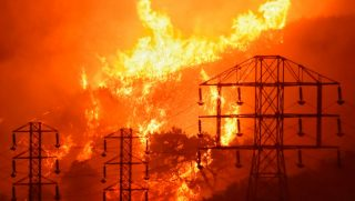 In this Dec. 16, 2017, file photo, flames burn near power lines in Sycamore Canyon near West Mountain Drive in Montecito, California. The parent company of California's largest utility said on Jan. 4, 2019, it is assessing its finances and structure in its effort to confront a growing liability threat from wildfires blamed on the company. Pacific Gas & Electric Corp., could face billions of dollars in potential liability involving the fires in California, some of which have already been linked to equipment operated by the company.