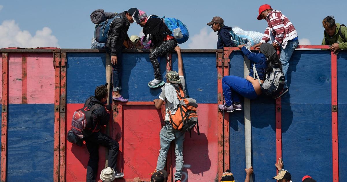 Migrant caravan men jumping over barrier
