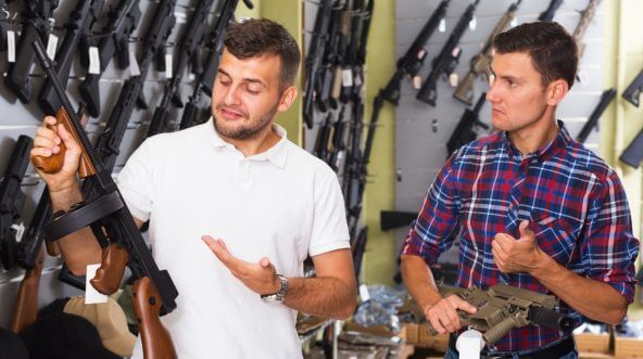 Two men choosing a gun.