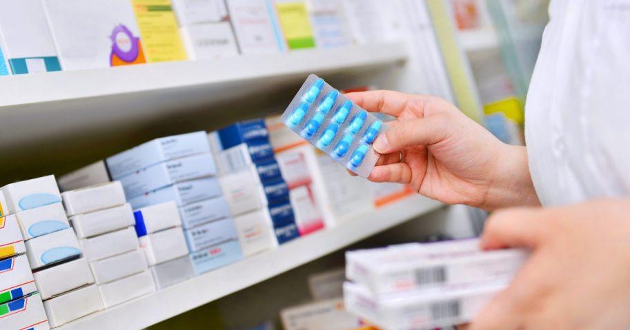 Pharmacist holding medicine box and capsule pack in pharmacy drugstore