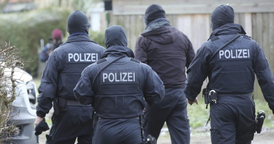Police officer in front of at building during a raid in the village Meldorf, Germany, Jan. 30, 2019. German authorities arrested three suspected Islamic extremist Iraqi men in the norther German costal region, on allegations they were planning a bombing.
