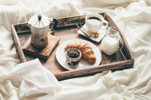 Crossiants and coffee sitting on a tray, placed on a bed.