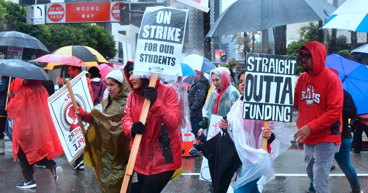 Thousands of teachers march in the rain through Los Angeles, California on Jan. 14, 2019, on the first day of the first teachers strike in 30 years targeting the Los Angeles Unified School District