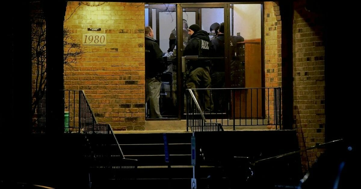 Investigators enter an apartment building where a man who police say fatally shot several people and injured police officers at a manufacturing plant in Aurora is believed to have lived.
