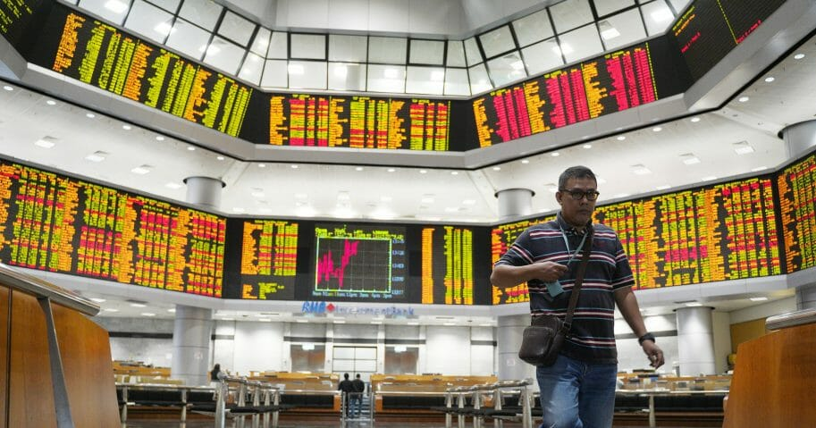 An investor walks in front of private stock trading boards at a private stock market gallery in Kuala Lumpur, Malaysia, Friday, Feb. 15, 2019.