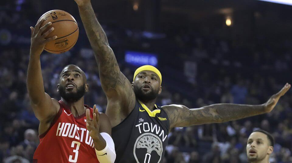 Houston Rockets point guard Chris Paul, left, lays up a shot past the Golden State Warriors' DeMarcus Cousins, center, in the first half of an NBA basketball game on Saturday, Feb. 23, 2019, in Oakland, California.